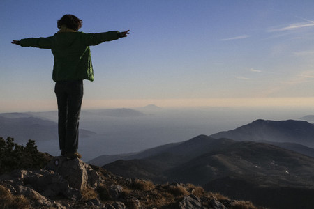 Carefree woman with arms outstretched on mountaintop Croatia