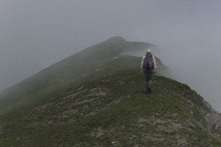 Man with backpack hiking on mystical foggy mountain Italy