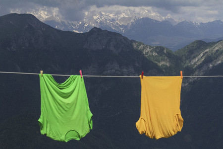 Bright green and yellow t shirts hanging on clothesline in mountains Slovenia