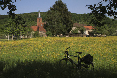 Bicycle parked in sunny idyllic meadow behind church Germany