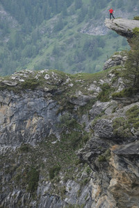 Man standing at the edge of rugged mountain cliff Italy