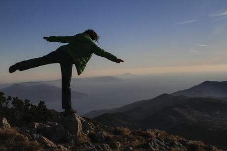 Playful woman balancing on mountaintop rock Croatia