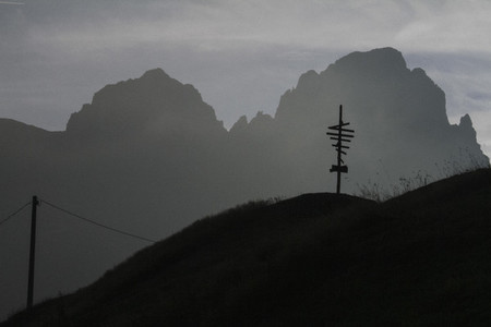 Silhouetted signpost and rugged mountains Italy