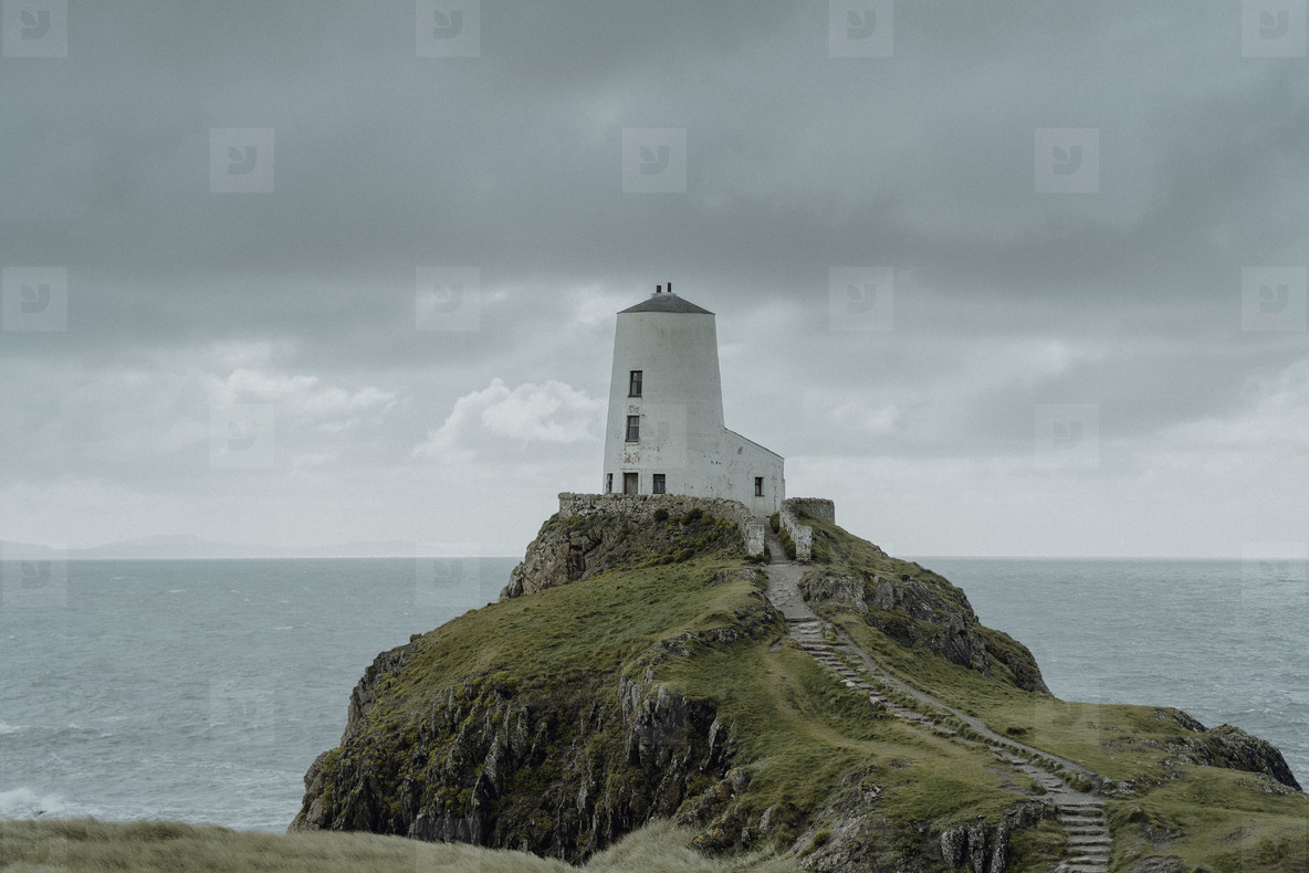 Lighthouse on ocean cliff under cloudy sky  Wales