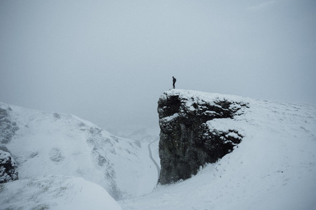 Hiker on remote snow covered cliff England