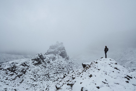 Hiker on snow covered rocks England