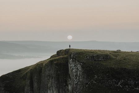 Hiker on cliff at sunrise England