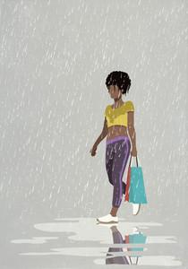 Woman with shopping bag walking in rain