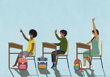 School children in face masks raising hands at classroom desks
