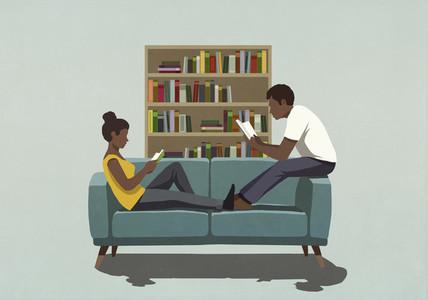 Couple reading books on living room sofa