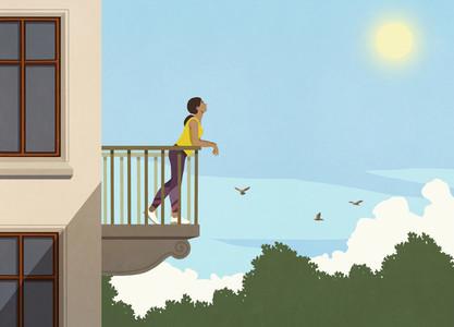 Woman enjoying sunshine from apartment balcony