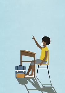 Schoolgirl in face mask raising hand at classroom desk