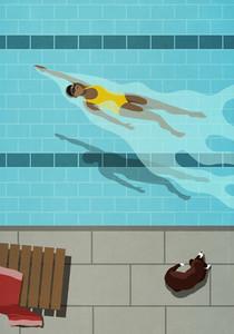 Dog watching woman swimming backstroke in swimming pool