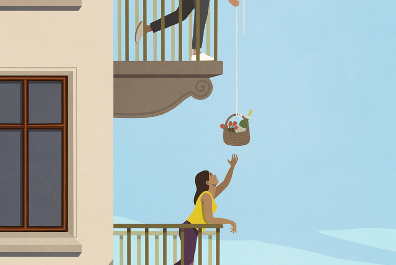 Man lowering gift basket to woman below on apartment balcony