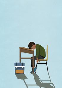 Exhausted schoolboy sleeping on classroom desk