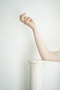 Woman039 s arm leaning on pillar against white background