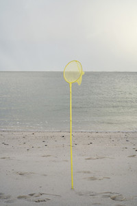 Yellow fishing net in sand on ocean beach