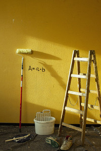 Ladder and paint supplies at vibrant yellow wall
