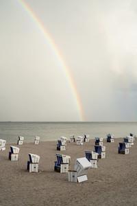Rainbow over cabanas on tranquil ocean beach Germany