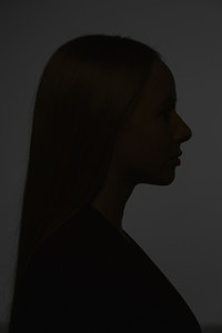 Dark silhouette young woman on black background