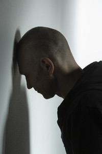 Frustrated man leaning head against wall
