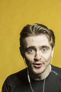 Portrait wide eyed man listening to music with headphones
