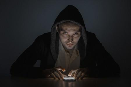 Portrait serious man using smart phone in the dark