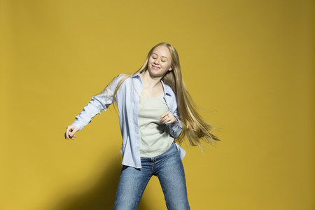 Portrait carefree young woman dancing on yellow background