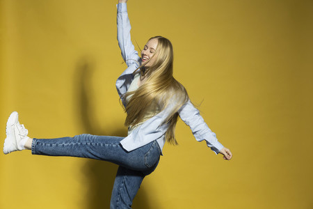 Carefree young woman dancing on yellow background