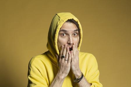 Portrait surprised young man in yellow hooded sweatshirt