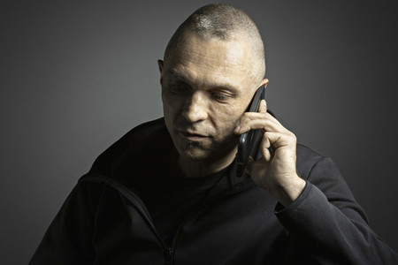 Mature man talking on smart phone against black background