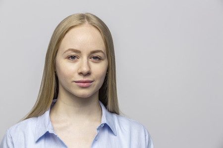 Portrait confident young woman on gray background