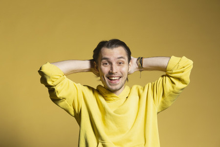 Portrait excited happy young man on yellow background