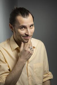 Portrait confident handsome man rubbing chin