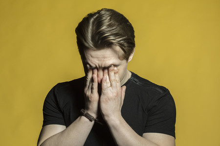 Tired stressed young man rubbing eyes on yellow background