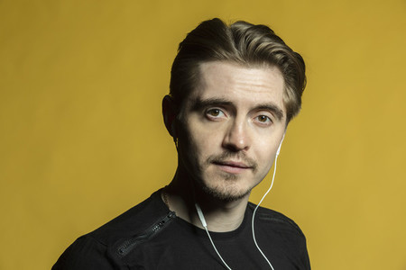 Portrait confident young man listening to music with headphones