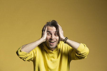 Portrait excited surprised man on yellow background
