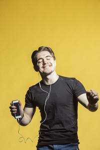 Carefree man with mp3 player listening and dancing to music