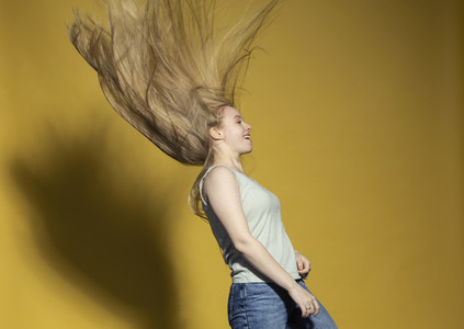 Carefree young woman flipping long blonde hair against yellow background