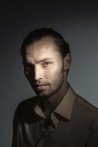 Studio portrait light over mysterious man