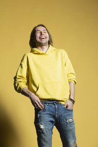 Happy man in jeans and hoody laughing against yellow background