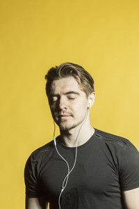 Serene man with headphones listening to music with eyes closed