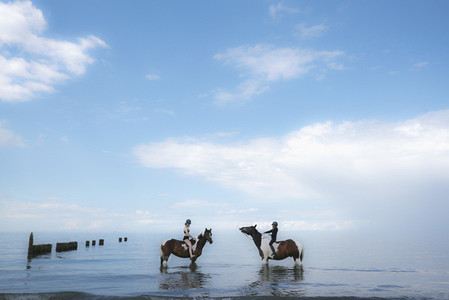 Girls riding horses in Baltic Sea Germany