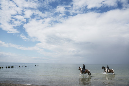 Girls riding horses in sunny Baltic Sea Germany