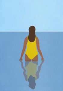 Woman in yellow bathing suit wading in blue ocean