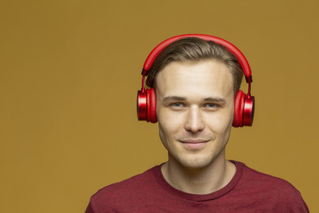 Studio portrait confident young man listening to music with headphones