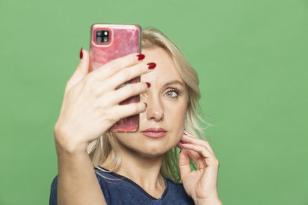 Beautiful blonde woman taking selfie on green background