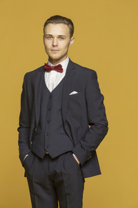 Studio portrait handsome young man in three piece suit with bow tie