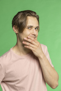 Portrait mischievous young man on green background