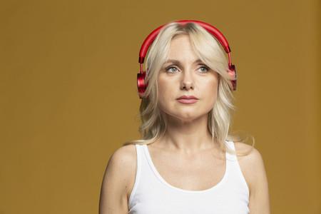 Studio portrait beautiful blonde woman listening to music with headphones